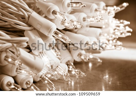 Seasonal background image of clear mini christmas lights in sepia tones.  Macro with extremely shallow dof. - stock photo
