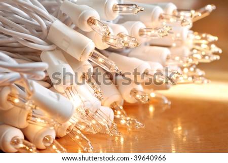 Seasonal background image of clear mini christmas lights on gold reflective background.  Macro with extremely shallow dof. - stock photo