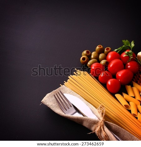 seasonal black table with pasta and cutlery - stock photo