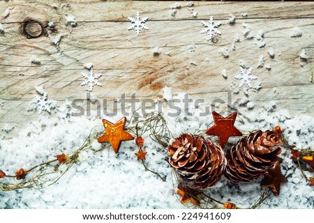 Seasonal Christmas background with pine cones draped in a garland of colorful orange stars sprinkled with winter snow against a rustic wooden background with snowflakes and copyspace - stock photo