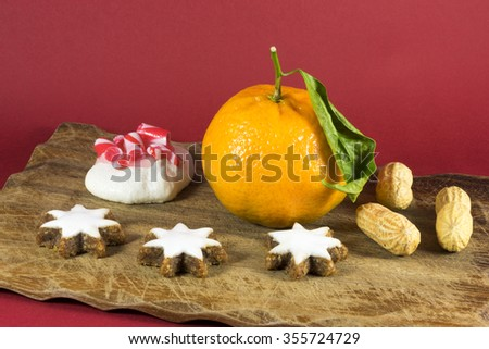 Seasonal Christmas still life home decoration with a fresh clementine, groundnuts or peanuts, white iced star cookies and a festive meringue with candy cane topping on a red background - stock photo