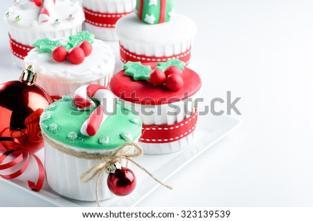 Seasonal festive christmas mini dessert cupcakes in traditional red green decorative symbols elements - stock photo