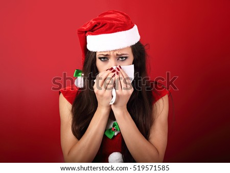 Seasonal flu. Unhappy frustration sick woman holding paper tissue near her nose and looking down in christmas night on red background