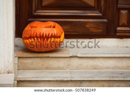 Seasonal holiday concept. Halloween pumpkin head on marble stairs and over wooden door background. Close up. Copy-space. Outdoor shot