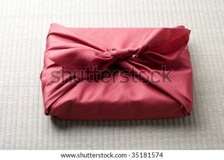 SEASONAL IMAGE-a gift box wrapped with red Japanese traditional cloth ; FUROSHIKI