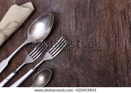 Seasonal old wooden table with cutlery. - stock photo