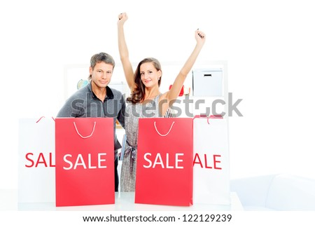 Seasonal sale: happy couple holding shopping bags inside of a store. - stock photo