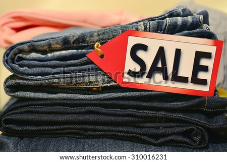 """Seasonal sale. Pile of clothes with """"sale"""" label. Shopping, black friday, columbus day sale, labor day sale - stock photo"""