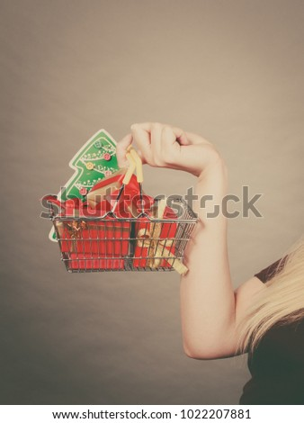Seasonal shopping, sales during winter xmas time concept. Woman hand holding shopping cart trolley with christmas tree and gifts