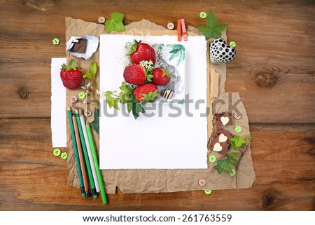 Seasonal summer composition with leaves, ripe strawberries and chocolates with heart shapes next to pencils over white background sheet of paper placed on brown paper and aged, weathered wood - stock photo