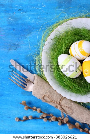 Seasonal table with cutlery and easter eggs. Easter holiday background. - stock photo