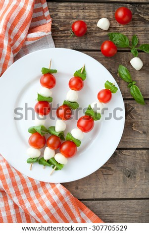 Seasonal traditional Italian caprese salad skewers with tomatoes basil and mozzarella cheese on white dish, rustic table background. Rustic style and natural light - stock photo