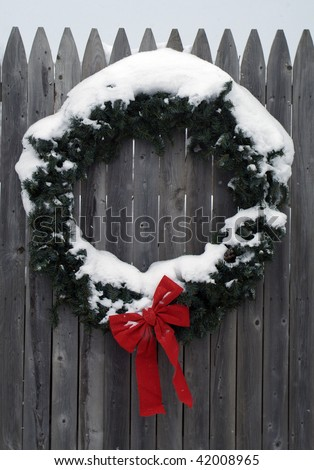 Seasonal Winter Christmas Wreath decoration on a fence as snow flakes come down - stock photo