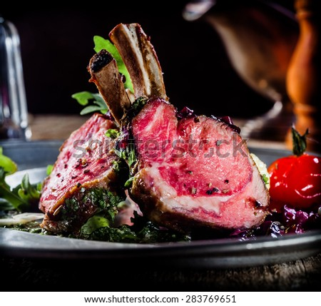 Seasoned roast rack of lamb with rare cooked cutlets from the rectangle carved and served with fresh salad and baby boiled potatoes for a gourmet country or rustic dinner - stock photo