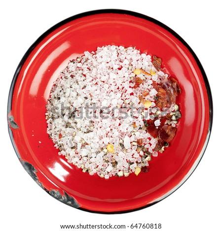seasoned sea salt in enamel red plate, isolated on white - stock photo
