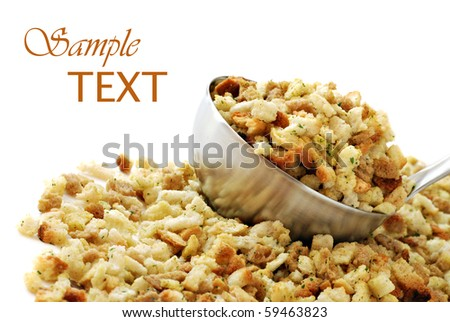 Seasoned stuffing mix spilling from stainless steel ladle on white background with copy space.  Macro with shallow dof. - stock photo