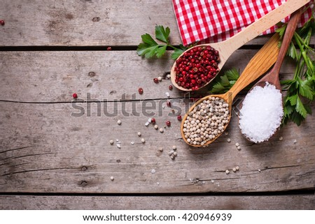 Seasoning for cooking. Red and white pepper and sea salt in wooden spoon on aged wooden background. Food ingredient. Selective focus. Place for text. Flat lay. Top view. - stock photo