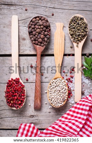 Seasoning for cooking. Red, white and allspice pepper and sea salt in wooden spoon on aged wooden background. Food ingredient. Selective focus. Flat lay. Top view. - stock photo