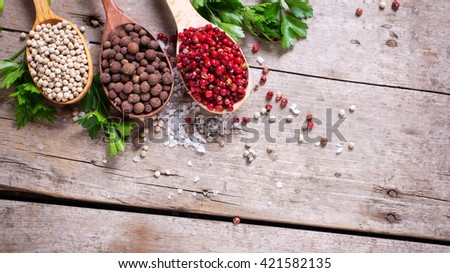 Seasoning for cooking. Red, white and allspice pepper  in wooden spoons on aged wooden background. Food ingredient. Selective focus. Flat lay. Top view. Place for text. Toned image. - stock photo