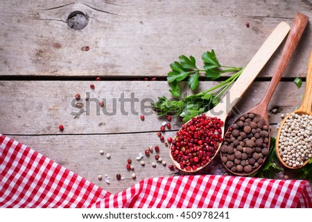 Seasoning for cooking. Red, white and allspice pepper in wooden spoons on aged wooden background. Food ingredient. Selective focus. Flat lay. Place for text. - stock photo