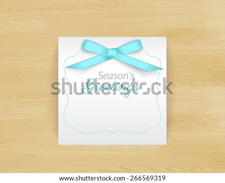 Seasons greetings white card with ribbon on wooden textured table. Template illustration. Free font Lato and Parisienne - stock photo