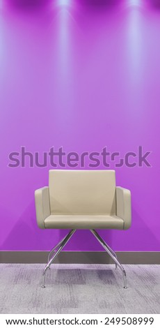 Seat against vibrant wall. - stock photo