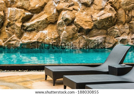seat by the swimming pool with stone background - stock photo