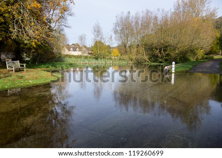 Seat overlooking a deep river at road ford on Shill Brook at Shilton Oxfordshire - stock photo