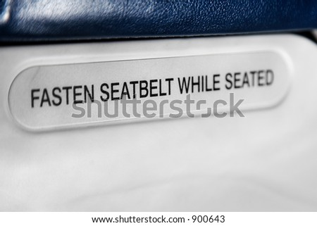 seatbelt sign on the back of the airplane's seat - stock photo