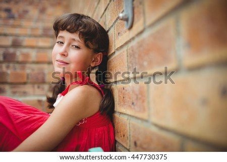 Seated brunette girl looking at the camera against brick walls - stock photo