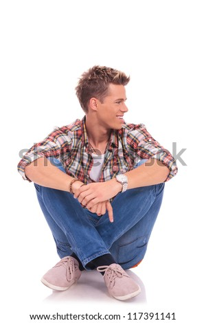 seated casual young man looking to his side and smiling - stock photo