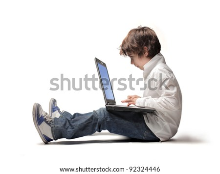 Seated child using a laptop - stock photo