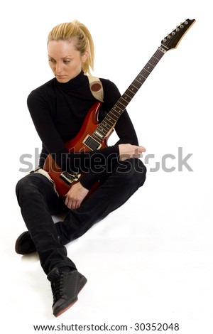 seated girl holding an electric guitar