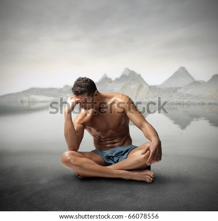 Seated handsome man reflecting with mountains on the background - stock photo