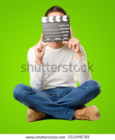 Seated happy young man using a clapperboard