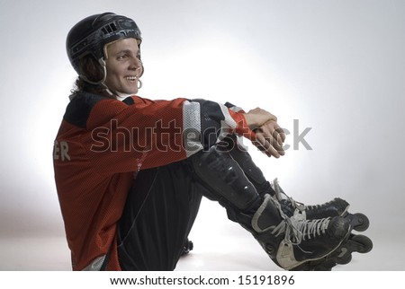 Seated hockey player smiles. He is wearing roller blades and hockey gear. Horizontally framed photograph - stock photo