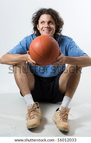 Seated man holds a basketball and smiles.  Vertically framed photograph - stock photo