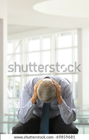 Seated Middle Aged Businessman Doubled Over with His Head in Hands in a modern business office. Vertical Format. - stock photo