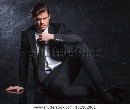 seated provocative elegant fashion man is fixing his black tie in studio