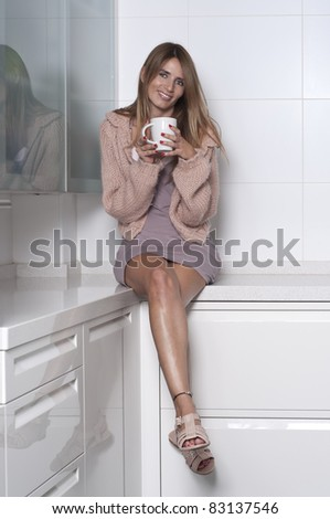 Seated woman in the kitchen with a cup