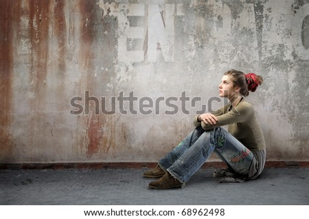 Seated woman wearing alternative clothes on a street - stock photo