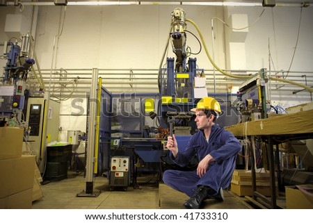 seated worker in industrial interior - stock photo