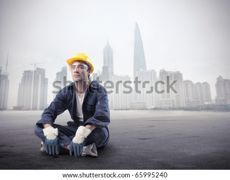 Seated worker with cityscape on the background - stock photo