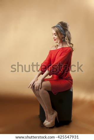 Seated young blonde girl wearing retro red dress, sixties makeup and hairstyle.