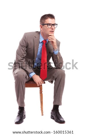 seated young business man looks away with his hand on his head. on a white background