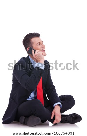 seated young business man talking on the phone and looking at his side on white background - stock photo