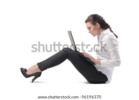 Seated young businesswoman using a laptop - stock photo