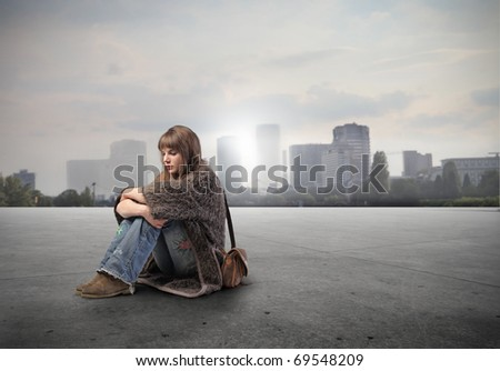 Seated young woman with cityscape on the background - stock photo