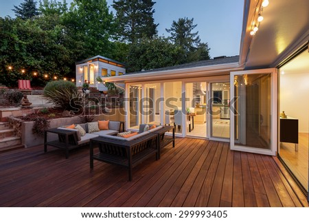 Seating arrangement, couch and sofa in front of contemporary home at night with open doors leading into home with wooden terrace in Zen Garden style with open floor plan and guest house. - stock photo