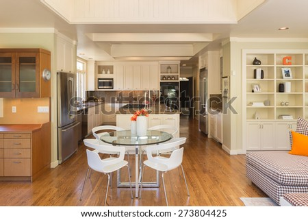 Seating arrangement in modern kitchen with double refrigerator, cabinets, cherry wooden floor and open ceiling. Kitchen in white with granite counter tops with stainless steel oven and stove. - stock photo